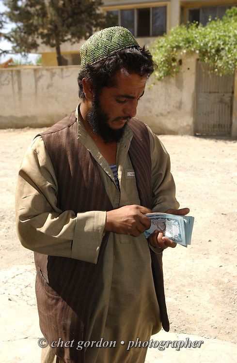 Truck delivery driver counts his payment in Kabul, Afghanistan on Thursday, May 23, 2002.
