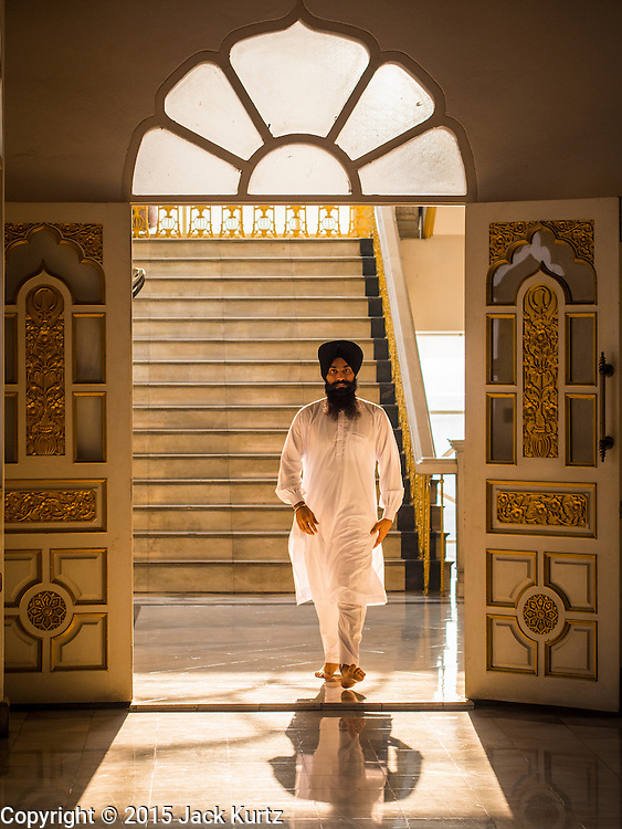 """08 FEBRUARY 2015  BANGKOK, THAILAND: A man walks into the Darbar Sahib (prayer hall) at Gurdwara Siri Guru Singh Sabha, the Sikh temple in Bangkok. Thailand has a small but influential Sikh community. Sikhs started coming to Thailand, then Siam, in the 1890s. There are now several thousand Thai-Indian Sikh families. Gurdwara Siri Guru Singh Sabha was established in 1913. Construction of the current building, adjacent to the original Gurdwara (""""Gateway to the Guru""""), started in 1979 and was finished in 1981. The Sikh community serves a daily free vegetarian meal at the Gurdwara that is available to people of any faith and background.    PHOTO BY JACK KURTZ"""
