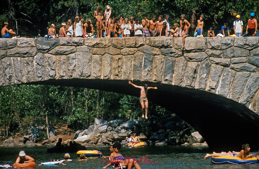 Youthful visitors to Yosemite National Park get together on the walkways of Stoneman Bridge to watch as a daredevil makes the plunge into the Merced River below.  July 19, 1988