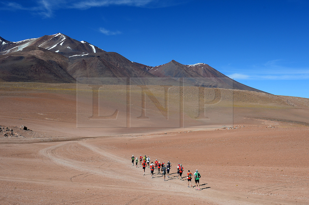 © Licensed to London News Pictures. 14/11/2013.<br /> <br /> Runners at or just after the start.<br /> <br /> Inaugural Volcano Marathon, Atacama Desert, Chile. The race took place in the Atacama Desert in Chile, beginning at an altitude of 4,400 metres (14,500 feet) in the vicinity of Lascar Volcano. It was a gruelling affair for many of the competitors who had to encounter some challenging hills and manage the impact of the heat and oxygen deprivation. The average altitude of the entire race was close to 4,000 metres and temperatures reached the mid 20s Celsius, or almost 80 Degrees Farenheit.<br /> <br /> Photo credit : Mike King/LNP<br /> <br /> Further information and link to video here: https://www.dropbox.com/s/0277bepxvo0t8il/Marathon%20copy.txt