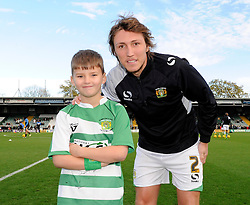 Yeovil Town's Luke Ayling has his photo taken with a young Yeovil Town mascot - Photo mandatory by-line: Dougie Allward/JMP - Tel: Mobile: 07966 386802 10/11/2013 - SPORT - FOOTBALL - Huish Park - Yeovil - Yeovil Town v Wigan Athletic - Sky Bet Championship
