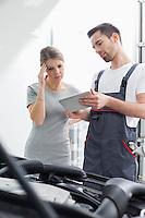 Male maintenance engineer showing digital tablet to worried customer at workshop