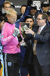 Nov 23, 2013; Kansas City, KS, USA; MLS president Mark Abbott presents the trophy to Sporting KC goalkeeper Jimmy Nielsen (1) after the MLS Eastern Conference Championship soccer game against the Houston Dynamo at Sporting Park. Sporting KC won 2-1. Mandatory Credit: Denny Medley-USA TODAY Sports
