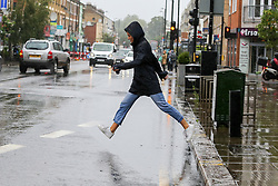 © Licensed to London News Pictures. 19/08/2020. London, UK. Erin Brook leaps over a large puddle of water in north London. According to the Met Office warmer weather with highs of 24 degrees celsius is forecasted for the rest of the week. Photo credit: Dinendra Haria/LNP