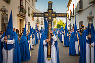 "Every holy week procession begins with a hooded man carrying a big cross. A line that for the biggest brotherhoods can be formed by thousands of ""nazarenos"" follows the cross. Cordoba, Spain."