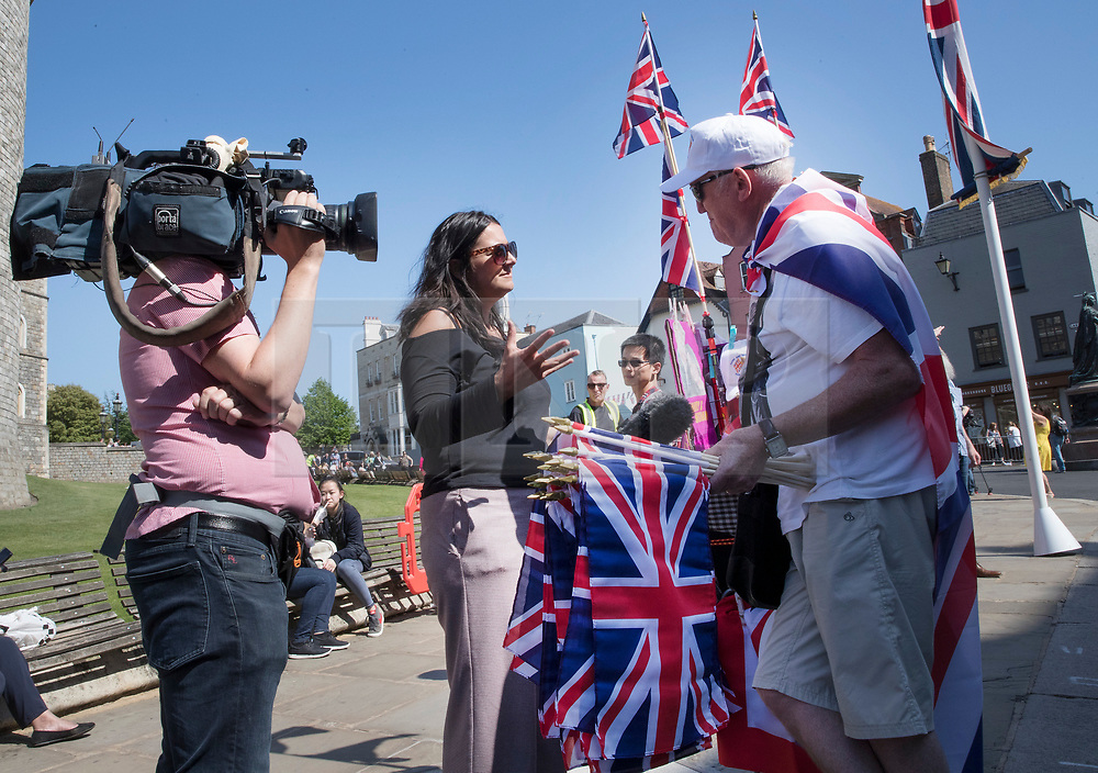 © Licensed to London News Pictures. 15/05/2018. Windsor, UK. A television reporter interviews a flag seller outside Windsor Castle ahead of the marriage of Prince Harry and Meghan Markle on Saturday. Photo credit: Peter Macdiarmid/LNP