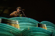 """Maryn Jacques of the Tiger Lillies plays the piano accordion behind a scrim at the Celebrate Brooklyn concert. The Tiger Lillies performed their song cycle based on Coleridge's """"Rime of the Ancient Mariner""""."""