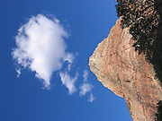 Photograph of a red rock mountain standing tall with blue sky and white clouds in the distance in Zion National Park on June 12, 2005 in Springdale, Utah. ©Paul Anthony Spinelli