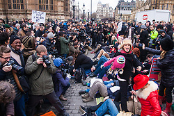 London, December 12th 2014. Porn and sex workers gather outside the Houses of Parliament for a mass sex simulation and face-sitting event in rotest against newly outlawed sex acts in the making of pornography in the UK. Under new Audiovisual Media Services Regulations 2014 rules, such acts as facesitting, spanking and female ejaculation are, among others, now banned from being shown  porn watched online. PICTURED: Hundreds of photographers crowd round a group of participants during a mass face-sitting demonstration.