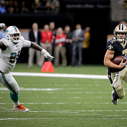 Aug 29, 2019; New Orleans, LA, USA; New Orleans Saints quarterback Taysom Hill (7) runs from Miami Dolphins defensive end Jonathan Ledbetter (98) during the second half of a preseason game at the Mercedes-Benz Superdome. Mandatory Credit: Derick E. Hingle-USA TODAY Sports