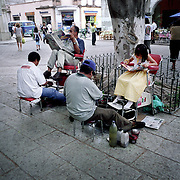 A young girl and older man get their shoes cleaned on the streets of Mexico City.<br />