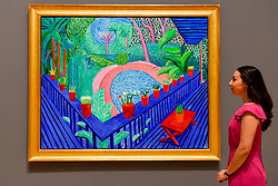 "© Licensed to London News Pictures. 06/02/2017. London, UK. A staff member views ""Red Pots in the Garden"" at the preview of the world's most extensive retrospective of the work of David Hockney at the Tate Britain, which will be on display 9 February to 29 May 2017. Photo credit : Stephen Chung/LNP"