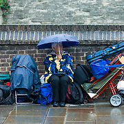 Woman from Morris dancing group sitting with umbrella in the rain
