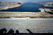 View northward (toward Cairo) from the top of the Aswan Dam.  Low slope toward the river Nile sheathed in cut stone.  Shadows of pedestrians at top.  Desert and river recede to the horizon.