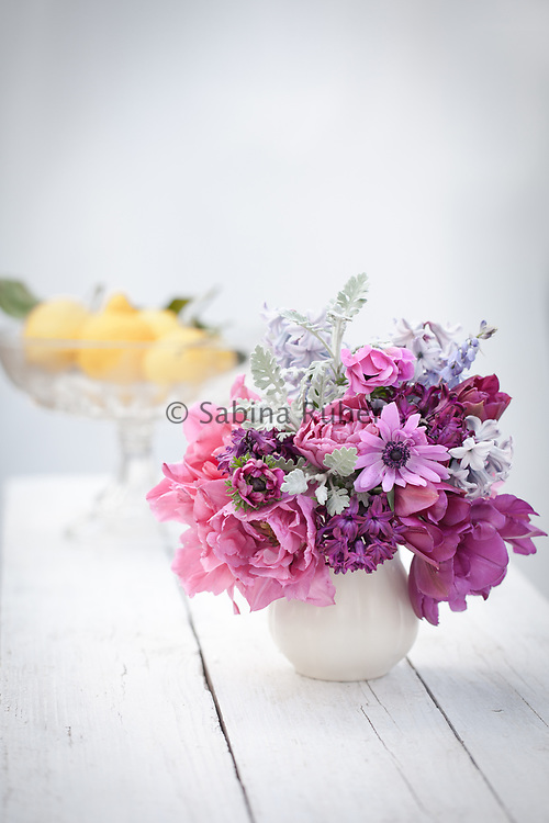 Spring flower arrangement with double tulips, anemones and hyacinths