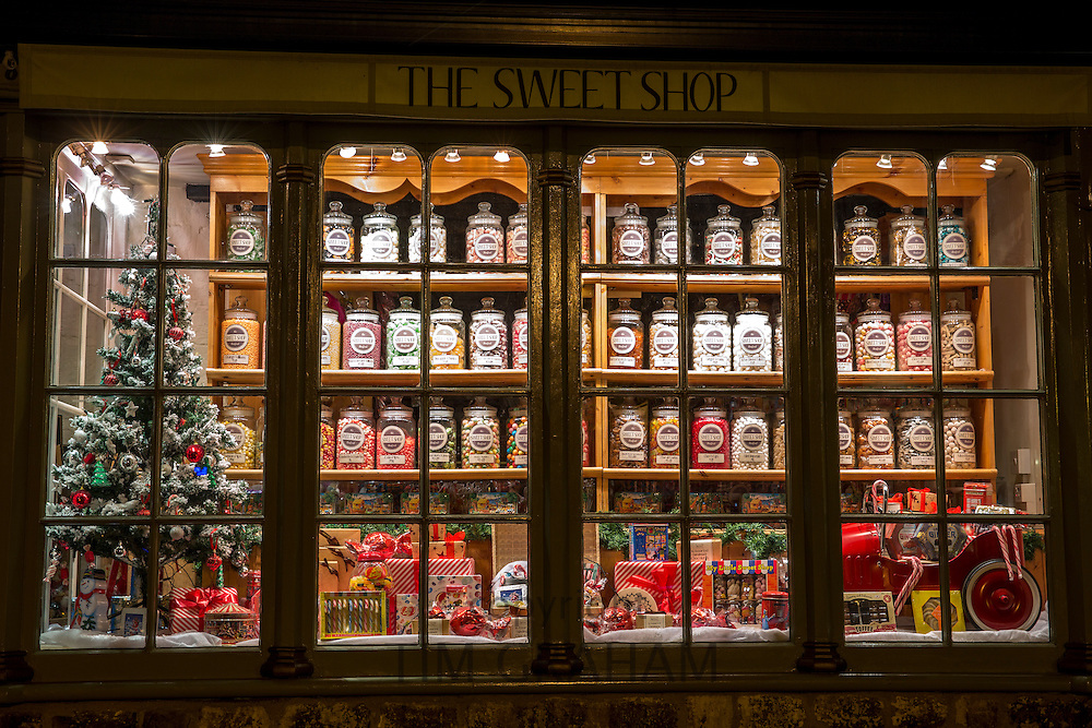 Window display of old traditional sweet and candy shop on Burford High Street at night, The Cotswolds, UK
