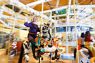Garden City, New York, USA. March 9, 2019.  DEBRA MULÉ, Nassau County Legislator, rides Nunley's Carousel during Unveiling ceremony of mural by painter Michael White, of close-up of a Nunley's Carousel horse. Event was held at historic Nunley's Carousel in its Pavilion on Museum Row on Long Island. After speeches by elected officials and members of Baldwin Civic Association and Baldwin Historical Society, and others, people enjoy free carousel rides and food.