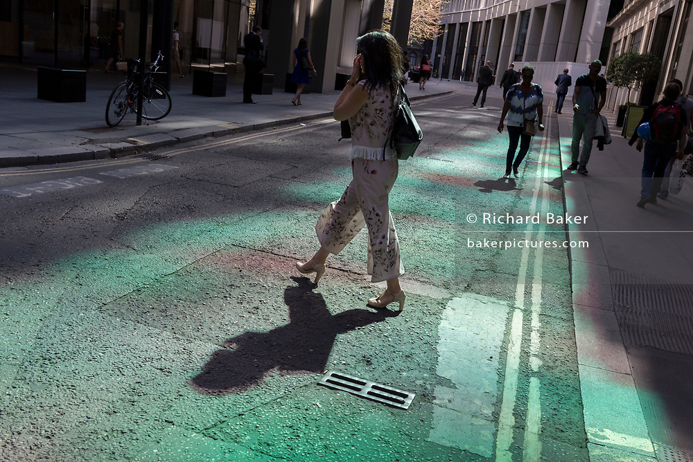 A lady walks through reflected light on Lime Street in the City of London, the capital's historic financial district, on 2nd August 2018, in London, England.