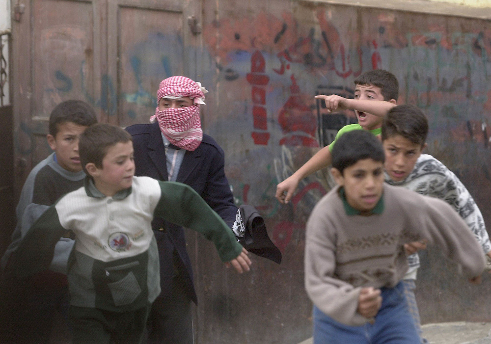 Palestinian children scream and gesture when running from  Israeli soldiers during clashes in the West Bank city of Hebron Friday October 27, 2000. Thousands of rock throwers and several gunmen clashed with Israeli soldiers throughout the West Bank and Gaza.