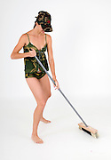 young woman in sexy military uniform with broom sweeps the floor