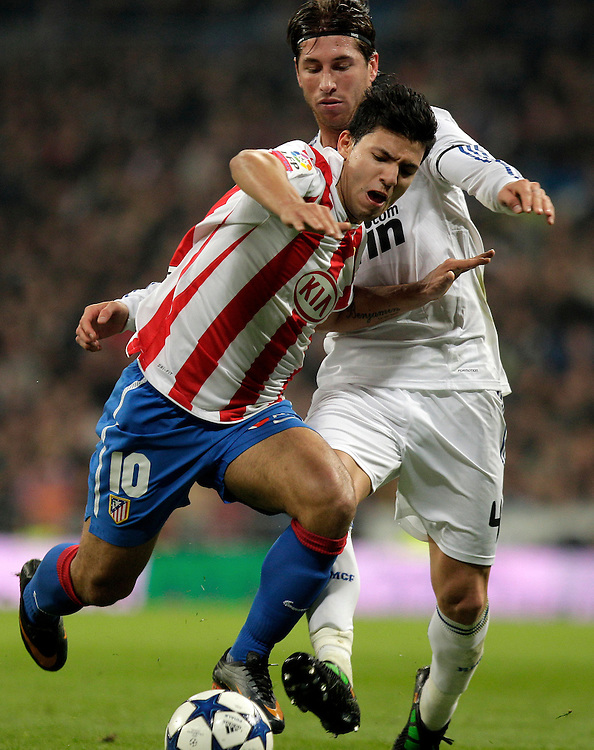 Atletico de Madrid's Sergio'Kun' Aguero from Argentina, left, vies for the ball with Real Madrid's Sergio Ramos, right, during a quarter final 1st leg Spanish Copa del Rey soccer match at the Santiago Bernabeu stadium in Madrid, Thursday, Jan. 13, 2011.