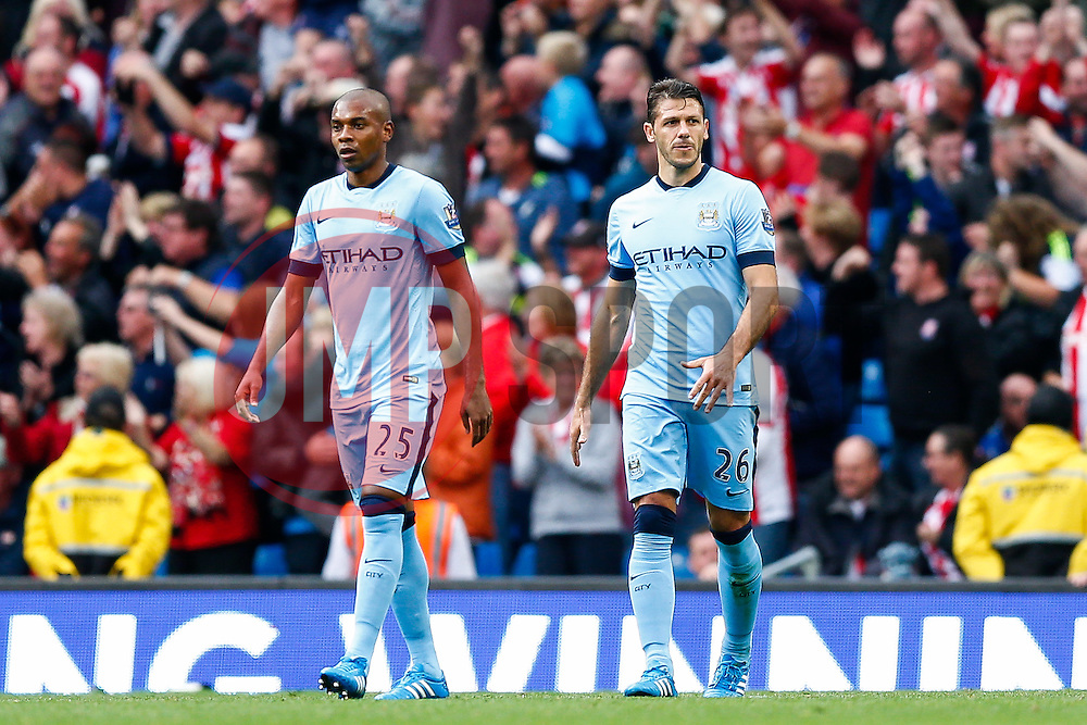 Fernandinho and Martin Demichelis of Manchester City look dejected after Mame Biram Diouf of Stoke scores a goal to give his side a 0-1 lead - Photo mandatory by-line: Rogan Thomson/JMP - 07966 386802 - 30/08/2014 - SPORT - FOOTBALL - Manchester, England - Etihad Stadium - Manchester City v Stoke City - Barclays Premier League.