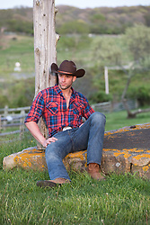 cool good looking cowboy sitting against a post on a ranch