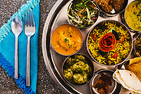 A traditional Indian lunch with rice, various curries, pickles, and vegetables at Vivenda Dos Palhacos in southern Goa, India.