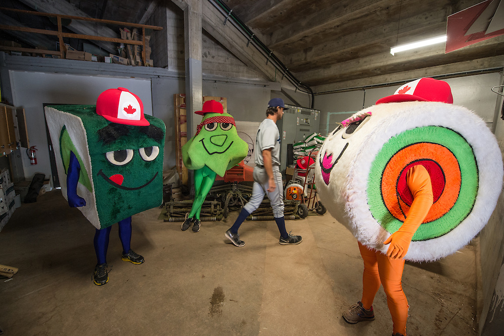 "An Everrett Aquasox player walks by the ""Sushi"" mascots while they wait under the stands before racing around the bases during a game between the Vancouver Canadians and the Everett Aquasox at Nat Bailey stadium."