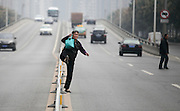XI'AN, CHINA - OCTOBER 16: (CHINA OUT) <br /> <br /> Crossing Main road is a danger every day<br /> <br /> A woman strides across guard bar to cross the road on October 16, 2014 in Xi'an, Shaanxi province of China. 109 passengers used the guard bar to cross the road within 2 hours since there is no pedestrian crossing between a community and a bus station in Xi'an<br /> ©Exclusivepix