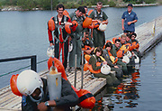 The first female NASA astronauts qualify in Water Survival School at Turkey Point, Florida. Here NASA astronaut candidates Anna L. Fisher and Sally Ride sit among their male classmates as they await their turn in a helicopter water pickup exercise.