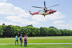 © Licensed to London News Pictures. 03/07/2019. LONDON, UK.  Tourists look on as a Coastguard Rescue helicopter takes off from Regent's Park after collecting equipment from a Children's Acute Transport Service (CATS) ambulance on behalf of nearby Great Ormond Street Hospital.  The helicopter will make the journey to collect a sick child who will be brought back for treatment at Great Ormond Street as travel by road would take too long.  Photo credit: Stephen Chung/LNP