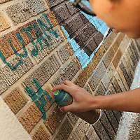 M.J. Torrecampo signs her name to the mural she and fellow artist Lujan Perez painted on Broadway Street in Tupelo.