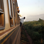 "Passengers lean outside of the train as it makes one of 30 station stops between Nairobi and Mombasa. The approximately 300 mile journey took 16 hours this trip. Also known as the ""Lunatic Express"", It was the railway line that built Kenya, linking the port town of Mombasa through the capital, Nairobi, to the shores of Lake Victoria and on to the Ugandan capital, Kampala. It cost $5m (in 1894 money) and countless workers died during its construction. There were derailments, collisions, tribal raids and attacks by lions. Yet despite becoming one of Kenya's national treasures and a vital economic artery for east Africa, the railway now lies in a state of disrepair. A South African consortium has taken it over and plans to invest millions, returning it to its former glory. But there has been a row over the railway's financing which may yet derail the .project. .."