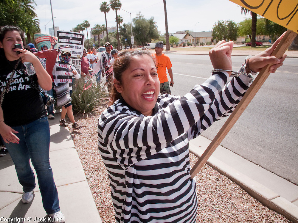 02 MAY 2009 -- PHOENIX, AZ: Selena Lopez (CQ) wore handcuffs and stripes to represent the undocumented immigrants incarcerated in Sheriff Joe Arpaio's jails Saturday. About 1,500 people opposed to Sheriff Joe Arpaio's treatment of prisoners and his high profile crime suppression anti-undocumented raids, marched from his office to downtown Phoenix to the jail complexes on Durango in south Phoenix Saturday. Photo by Jack Kurtz
