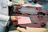 """ROME, ITALY - 15 OCTOBER 2018: A leather artisan working for FENDI explains the leather bags production process to students during the LVMH Journées Particulières exhibition at the Fendi headquarters in Rome, Italy, on October 15th 2018.<br /> <br /> The LVMH Journées Particulières is is a series of exhibitions that show the creations and history of the LVMH fashion houses. The driving theme behind the Journées Particulières is to allow the general public to discover the inner workings of the Houses which are part of the LVMH heritage.The LVMH Journées Particulières exhibition by fashion house FENDI takes place at their headquarters at the Palazzo della Civiltà Italiana, also called the """"Colosseo Quadrato"""" (Square Colosseum),  an outstanding jewel of the 20th century Roman architecture."""
