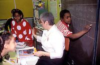 Teacher with junior school pupils in USA classroom.