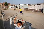 Children play on Thursday, Apr. 16, 2009 in Ventanilla, Peru.