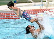 Auburn resident Joe Hanna throws his son Mark (6) into the air Monday afternoon at Samford Pool.  Auburn City opened both the Samford and Drake pools for the season on Monday, May 23.