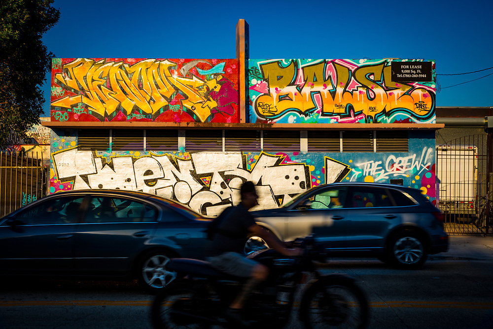 Traffic zips by a graffiti-covered Art Deco building on North Miami Boulevard in Wynwood