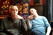 Two teenagers sitting in a coffee shop smoking spliffs, Amsterdam, Netherlands, 2000's