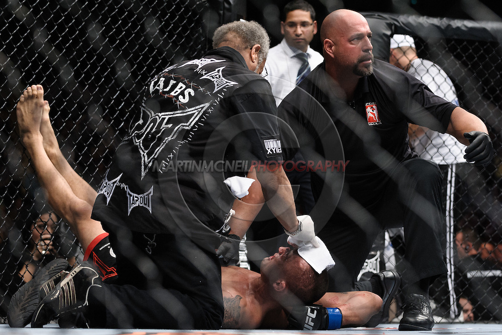 """MANCHESTER, ENGLAND, NOVEMBER 14, 2009: Referee Dan Miragliotta (facing) anc cutman Leon Tabbs check on Denis Kang after his loss at """"UFC 105: Couture vs. Vera"""" inside the MEN Arena in Manchester, United Kingdom."""