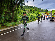 09 AUGUST 2018 - KAENG KRACHAN, PHETCHABURI, THAILAND: Royal Thai Army soldiers run down a flooded rural road at a construction site for an emergency spillway being built for the Kaeng Krachan Dam. The Phetchaburi River flows from Kaeng Krachan Dam to the Gulf of Siam through several towns including Ban Lat, Phetchaburi (the capital of Phetchaburi province) and Ban Laem. Government officials have warned residents of those towns that their towns will flood because the reservoir behind the dam is approaching capacity. Ban Lat and Phetchaburi could be flooded for several weeks. Residents of Ban Laem have been warned that their community could be inundated for over a month. Dams in Kanchanaburi province, west of Phetchaburi, are also approaching capacity and flooding is also expected in that area.   PHOTO BY JACK KURTZ