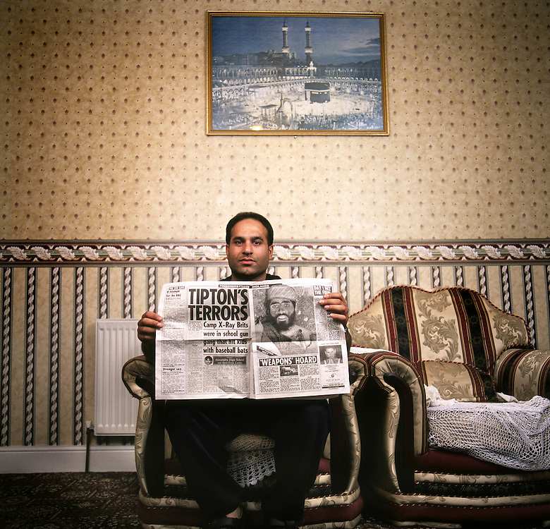 Murtza Rasul, 32, holds a newspaper article that allegedly shows his brother, Shafiq Rasul, with a bullet wound after he was captured in Afghanistan in 2001. Photographed at the family home in Tipton in the East Midlands, UK. Shafiq Rasul is being detained by the US at the Guantanamo Bay military base at the edge of Cuba.