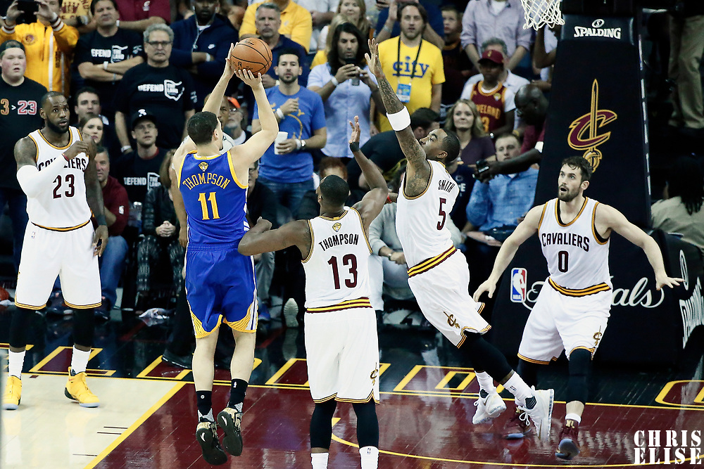 09 June 2017: Golden State Warriors guard Klay Thompson (11) takes a jump shot over Cleveland Cavaliers guard JR Smith (5) and Cleveland Cavaliers center Tristan Thompson (13) and Cleveland Cavaliers forward Kevin Love (0) during the Cleveland Cavaliers 137-11 victory over the Golden State Warriors, in game 4 of the 2017 NBA Finals, at  the Quicken Loans Arena, Cleveland, Ohio, USA.