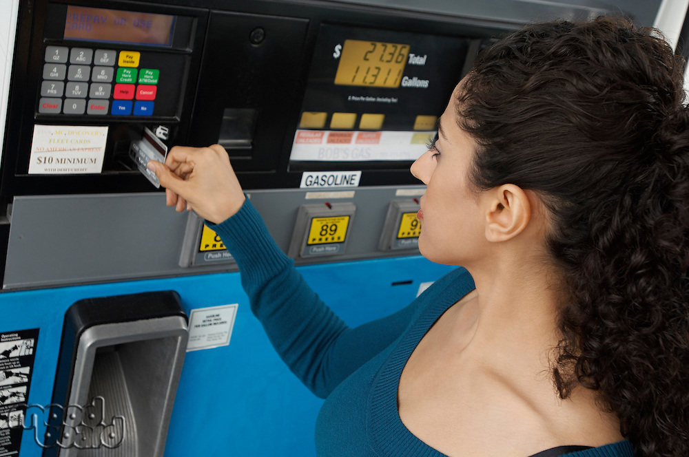 Woman paying with credit card at gas pump