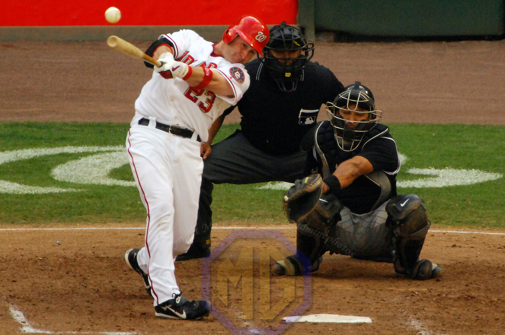 21 July 2007:  Washington Nationals catcher Brian Schneider (23) hits a single to right field in the 5th inning as Colorado Rockies catcher Yorvit Torrealba (8) and home plate umpire Adrian Johnson watch the play.  The Nationals defeated the Rockies 3-0 at RFK Stadium in Washington, D.C.  ****For Editorial Use Only****