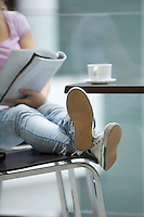 Young woman sits with feet up reading magazine