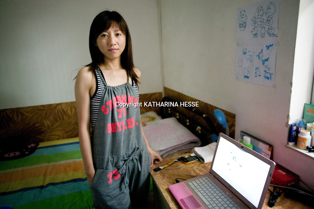 BEIJING, JULY-22, 2010  : A YOUNG WOMAN STANDS IN HER TINY ROOM IN THE BASEMENT OF A HIGH RISE.