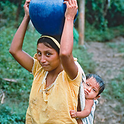 A Mayan mother balancing a  ceramic pot of water on her head while carring child on her back, Toledo District, Belize